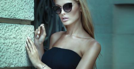 Fashionable blonde woman posing outdoor, wearing elegant mini dress and sunglasses. Stock Photo
