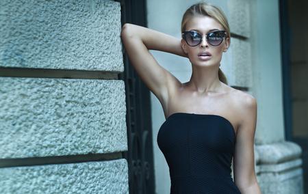 Fashionable blonde woman posing outdoor, wearing elegant mini dress and sunglasses. Foto de archivo