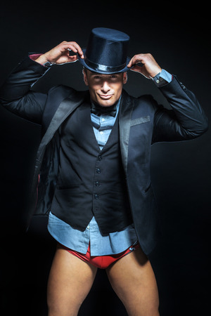 Handsome elegant man posing in suit and hat. Black background. photo