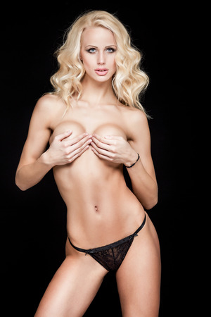 beautiful nude women: Sexy young blonde woman posing naked, looking at camera. Studio shot. Black background. Girl with perfect body. Stock Photo