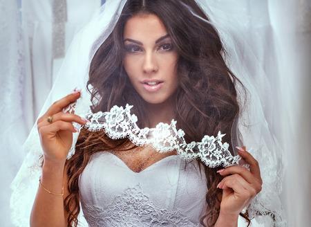 Beautiful brunette woman posing in fashionable white wedding dress. Studio shot.