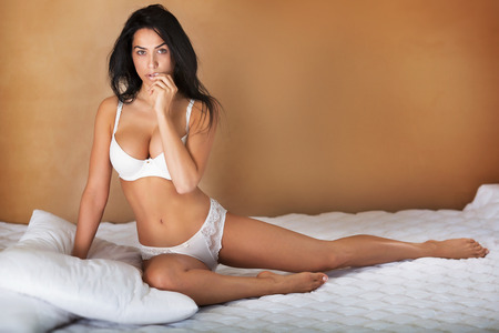 Sensual beautiful woman posing in white lingerie in bedroom. Girl sitting on bed. Perfect slim body. Stock Photo