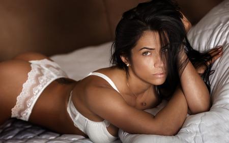 culo: Sensual mujer hermosa que presenta en ropa interior blanca en el dormitorio. Niña en la cama. cuerpo delgado perfecto.