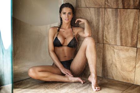 cuerpos desnudos: hermosa mujer morena sexy en bikini negro sentado bajo la ducha. Cuerpo perfecto.