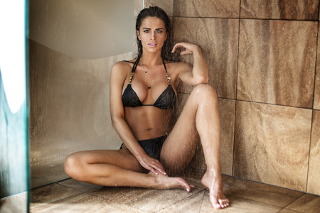 naked young people: Sexy beautiful brunette woman in black bikini sitting under shower. Perfect body. Stock Photo