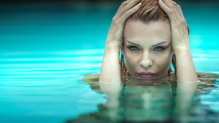 Beauty portrait of attractive blonde woman in swimming pool. Holidays. Stock Photo