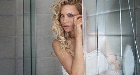 morning routine: Natural beautiful blonde woman posing in white towel in bathroom. Morning routine. Indoor photo. Stock Photo