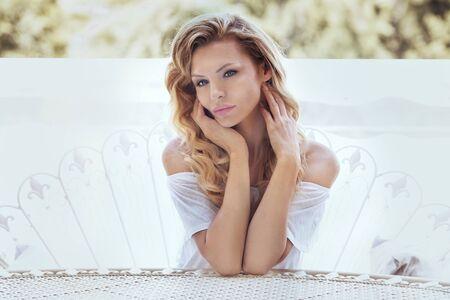 natural looking: Natural blonde woman relaxing,looking at camera. Sunny day. Stock Photo