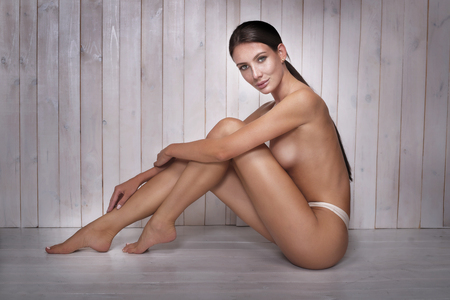 naked woman: Beautiful natural naked woman sitting on the wooden floor. Side view. Natural look. No makeup.