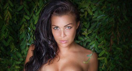 fille nue sexy: Belle femme naturelle posant nue sur les plantes vertes, regardant la caméra. Été abattu.