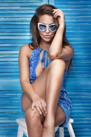 blue wall: Fashionable adult beautiful woman posing, looking at camera, wearing sunglasses. Blue background. Studio shot. Stock Photo