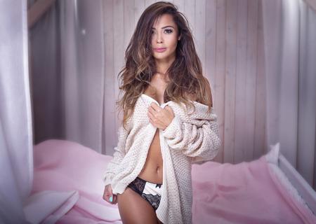 Beautiful young natural woman with long hair posing, looking at camera. Stock Photo