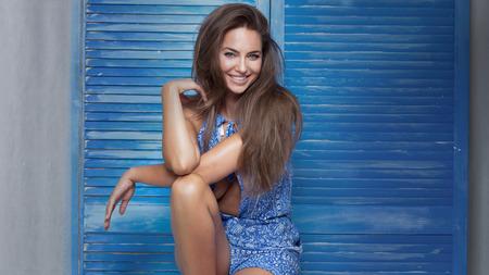 femme brune sexy: Sourire belle femme brune posant sur fond bleu en studio.