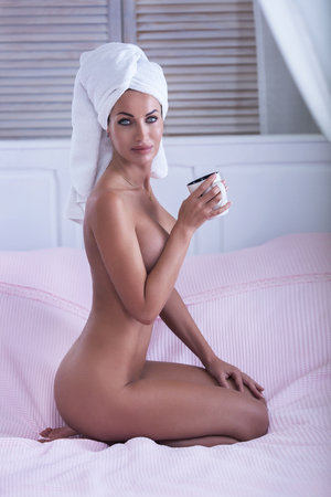 naked woman: Attractive beautiful woman with white towel on head sitting naked in bedroom, drinking coffee.
