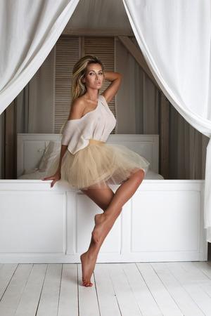 luz natural: Moda rubia hermosa dama posando en falda corta. Interior del hogar. Foto de archivo