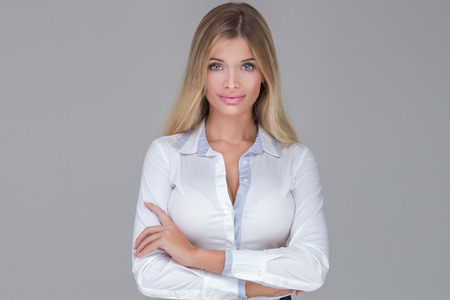 Office women: Beautiful blonde businesswoman looking at camera, posing in studio.