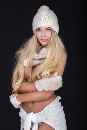 nude little girls: Blonde sexy woman in fashionable winter cap, scarf, gloves. Studio photo.