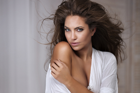 Sensual brunette woman posing in white, looking at camera. Beautiful lady. photo