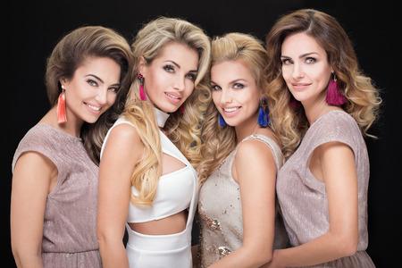 Portrait of four beautiful adult ladies. Glamour makeup. Elegant look. photo