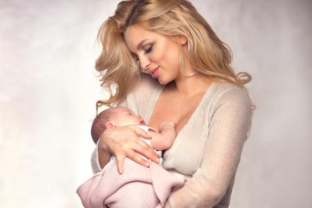 Young beautiful mother holding little baby girl. Studio shot.