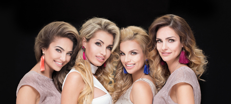 Portrait of four beautiful adult ladies. Glamour makeup. Elegant look.