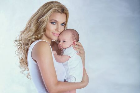 beautiful mother: Young beautiful mother holding little baby girl. Studio shot.