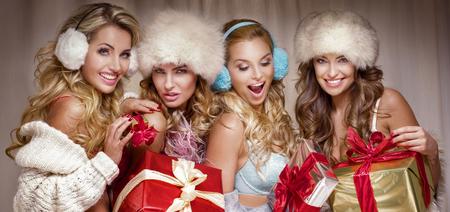 Beautiful sexy group of Santa girls. Ladies holding christmas gifts. photo
