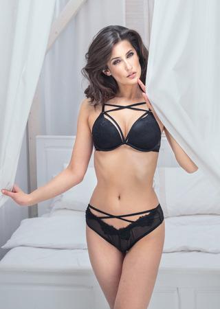 Sensual young brunette woman in black lingerie posing in bedroom.