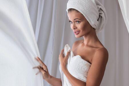 Blonde beautiful caucasian woman in white towel relaxing. Stock Photo
