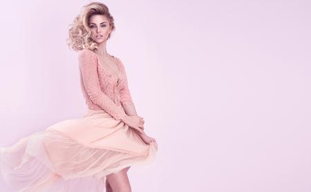 Attractive blonde beautiful woman posing on pink background, romantic look. Archivio Fotografico