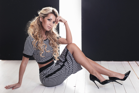 Elegant blonde attractive woman posing, wearing fashionable clothes and high heels.