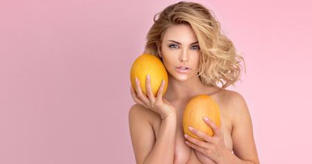 fille sexy nue: Sexy jeune femme blonde avec corps parfait posant avec du mangue frais, fond pastel rose.