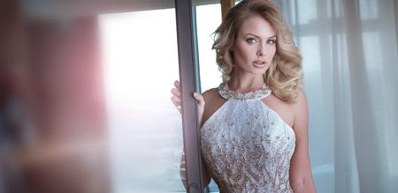 Sexy elegante mujer caucásica rubia posando en vestido hermoso.