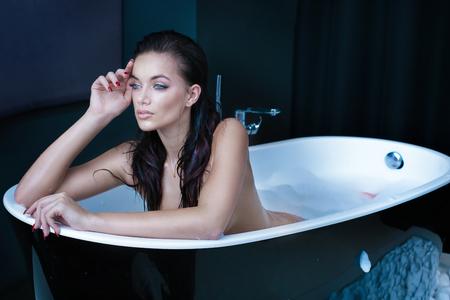 セクシーな白人女性のモダンなバスルームで入浴。