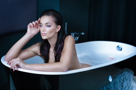 Sexy Kaukasische vrouw nemen bad in moderne badkamer. Stockfoto