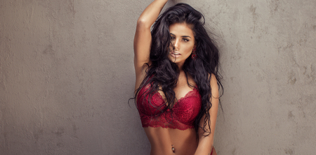 Sexy lady in lace lingerie witn long black hair looking at camera.
