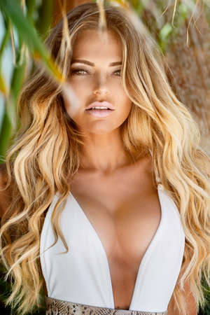 Beautiful blonde woman in white swimsuit with tanned body sensual posing between palm trees.