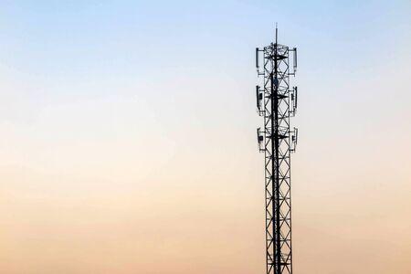 transmit: Telecommunication cellular tower on twilight background. Used to transmit television and telephone signal Stock Photo
