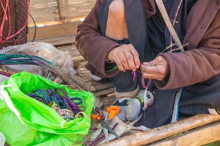 anklet: Old hill tribe woman make a handicraft bracelet at Doi Ang Khang Chiang Mai