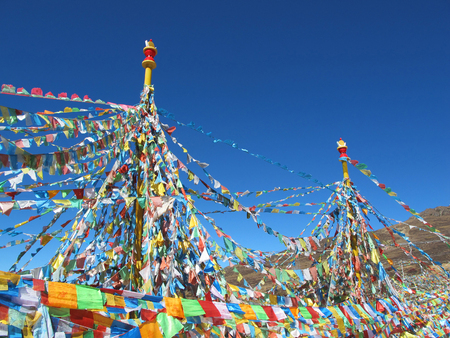 mantra: tibetan flags with mantra on sky background Stock Photo