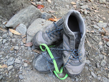 battered land: Old broken boot abandoned in a rubble background Stock Photo