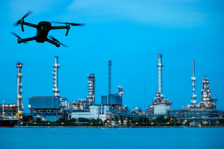 Modern RC Drone  Quadcopter with camera flying on Oil refinery plant site. double exposure Stock Photo