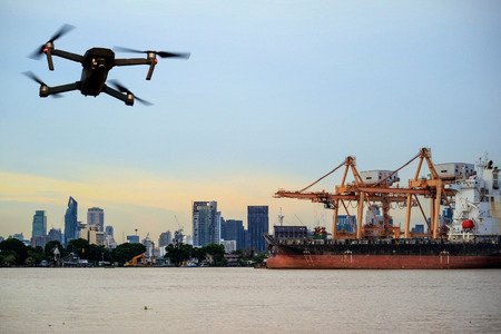 Modern RC Drone  Quadcopter with camera flying on container cargo ship at shipping port. double exposure
