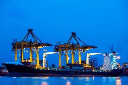 unloading: Shipping port. Cargo ship loading by crane Stock Photo