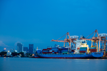 unloading: Shipping port. Logistics and transportation of international import export container cargo ship with crane bridge in harbor at twilight dusk for shipping and transportation industry Stock Photo