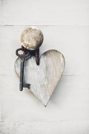 door lock love: Key with wooden heart hanged on the door handle