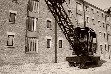 heave: Black, rail crane with brick wall in the background, in sepia Stock Photo