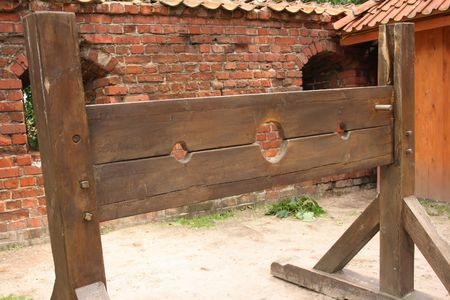 tribulation: Medieval wooden stocks used to torture people Stock Photo