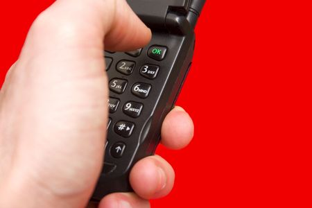 A hand dialing a mobile phone on a red backround Stock Photo - 382398