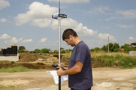 geodesist: Geodesist working on a terrain with gps